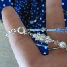 """Next, the 7.5"""" pearl insert strand is layered onto the same white base strand."""