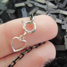 The loose end of the chain base strand is attached to a heart tab hook up clasp.