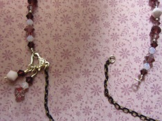 The back of the necklace will still be open. Use the opening to put the necklace on, without disturbing the charms you already attached.