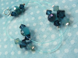 "This exclusive, one-of-a-kind insert is designed as an ""illusion"" style invisible strand. It includes teal blue fishing line and crystals. We may produce this strand in the furture, although it has an unfortunate tendency to kink permanently when worn often. Our other designs do not have this issue."