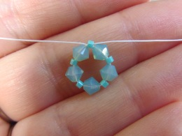 "Pull gently on both ends of the string to close the circle, and pull the design into a continuous ring. This beaded ring becomes the base you will use to build the ""arms"" of your starfish."