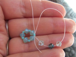 Loop the end of the string back into the seed bead below, creating an outer extension of your design, as pictured.