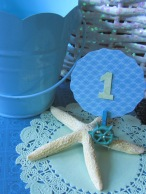Cluster a few colorful metal pails, floral arrangements in glittered baskets, and starfish table numbers to build your own, customized tablescape.