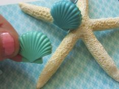 Step 4: Use glue gun to attach decorative shapes to starfish.